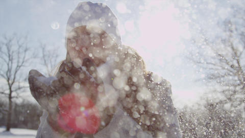 SLOW MOTION: Young woman blowing snowflakes over t Footage