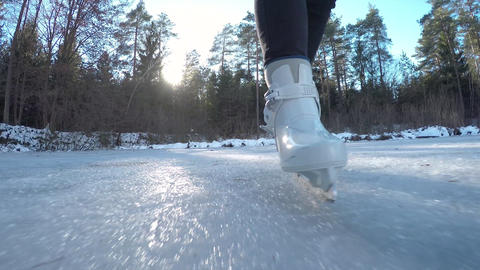 CLOSE UP: Ice skating on frozen pond in sunny fore Footage