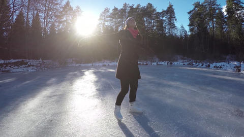 Young woman spinning on frozen lake on ice skates Live Action