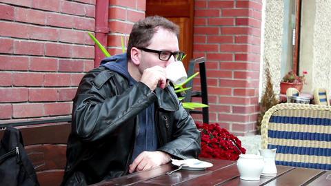 Man drinks coffee in sidewalk cafe Footage