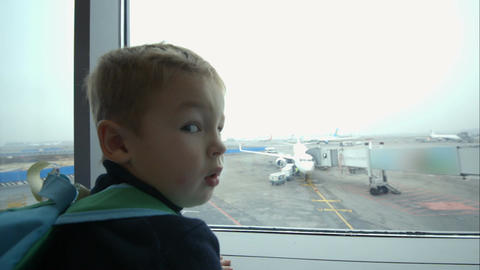 Little boy looking out window and pointing at plan Footage