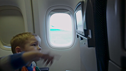 Little boy touching seat monitor in plane Live Action