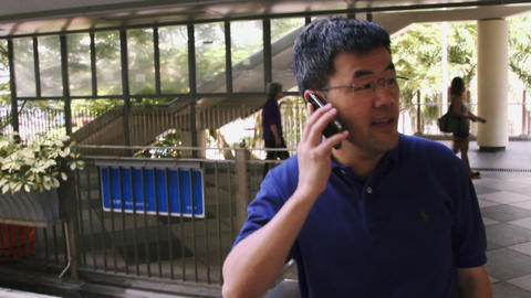 Mature man talking on mobile phone while standing near footbridge, Hong Kong, Ch Footage