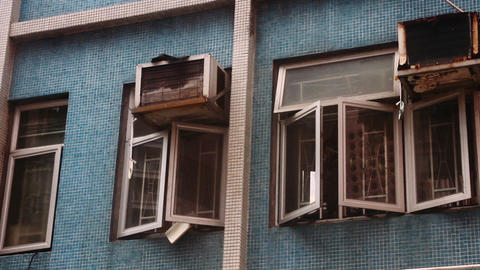 Exterior of house with damaged windows and air conditioner in Hong Kong, China Live Action