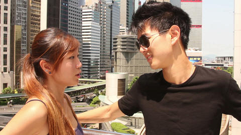Young man talking with young woman, modern buildings in background, Hong Kong, C Footage
