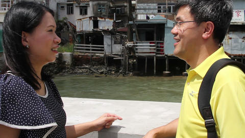 Mature couple talking while tourboat passing behind them at Tai O fishing villag Footage