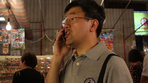 Mature man talking on mobile phone while standing in Fa Yuen Street Market, Hong Footage