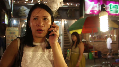Mature woman talking on mobile phone while standing in Fa Yuen Street Market, Ho Footage
