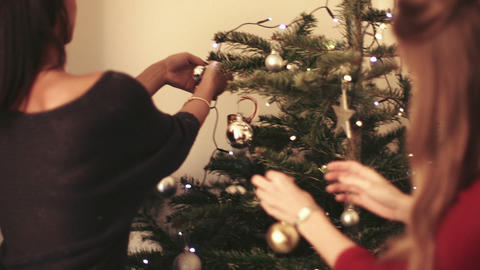 Young women decorating Christmas tree with Christmas ornaments Live Action