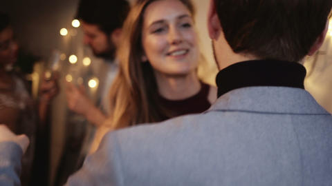 Young woman receiving gift from her friend during Christmas party Live Action