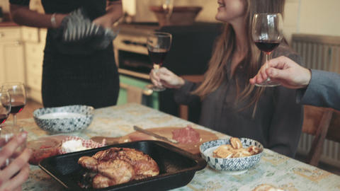Friends toasting and drinking red wine during Christmas dinner party Footage