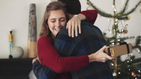 Young man giving gift to young woman at Christmas party Footage