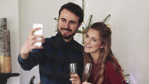 Young man and woman holding champagne flute and taking selfie during Christmas Live Action