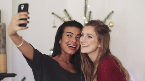 Young women taking selfie with mobile phone during Christmas party Live Action
