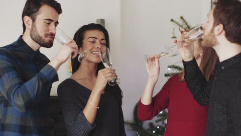 Young men and women toasting and drinking champagne during Christmas party Footage