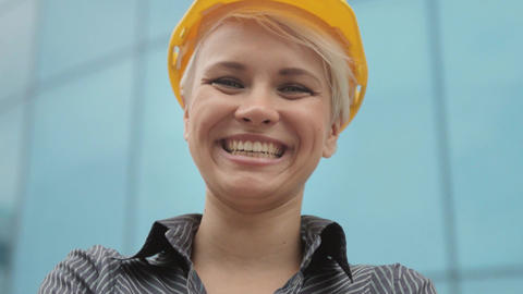 Portrait of female engineer with helmet smiling at camera Footage