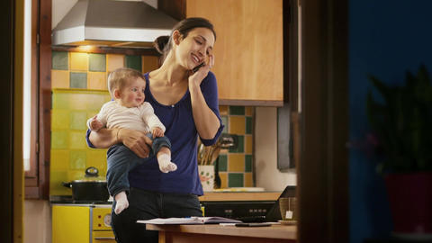 Multitasking Mother Cooking And Working Holding Li Footage