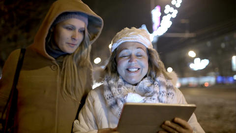 Two women walking with pad outdoor in the cold eve Footage