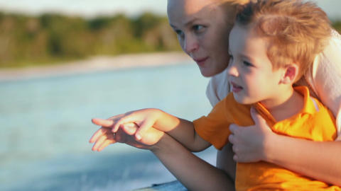 Mother and son enjoying sea travel by boat Live Action
