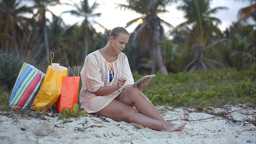 Woman after shopping using tablet pc on the beach Footage