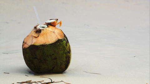 Coconut by the sea with female hand putting a stra Footage