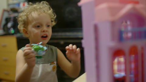 Happy little boy plays with toy helicopter Footage