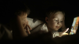 Two boys lying in bed at night and using pad Footage