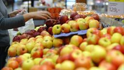 Putting apples in plastic bag in supermarket Live Action