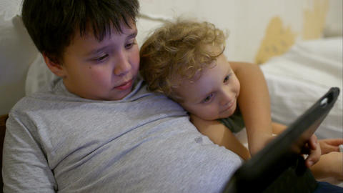 Two boys in bed with touch pad Footage