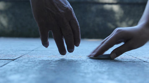 A Young And Old Hand Reaching For Money stock footage