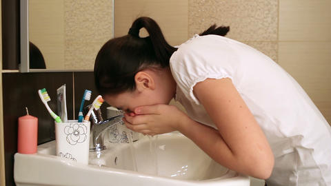 Young girl washing her face Footage