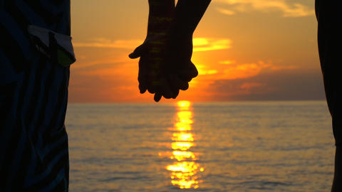 Couple in love holds hands at seaside sunset Footage