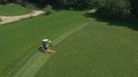 AERIAL: Tractor mowing on a grass field Footage