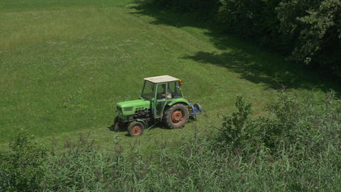 AERIAL: Flying towards the tractor mowing grass Footage