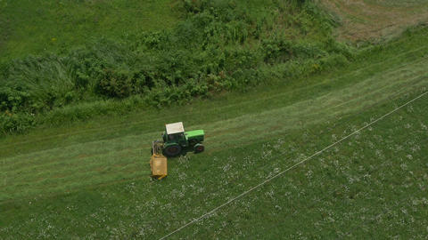 AERIAL: Tractor mowing in a big grass field Footage
