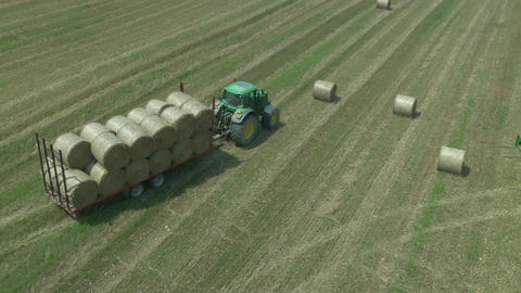 AERIAL: Tractor loaded with hay bales on a field Footage