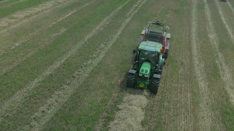 AERIAL: Making bales of hay with agricultural bale Footage