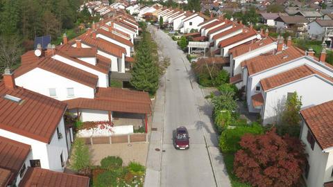 AERIAL: Car driving along quiet suburban street Footage