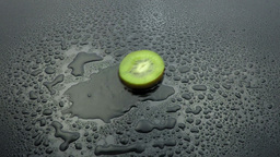slice kiwi fruit falling on wet Footage