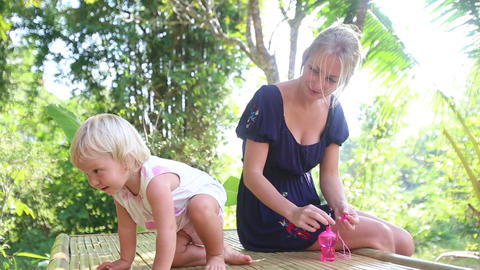 mother blowing bubbles for daughter Footage