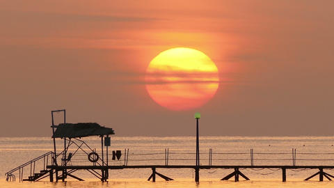 beautiful sunrise over pier in sea - telephoto len Footage