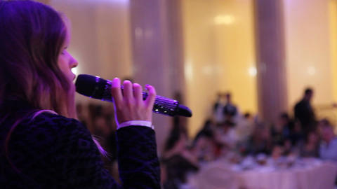 A singer with a microphone on stage at restaurant Footage