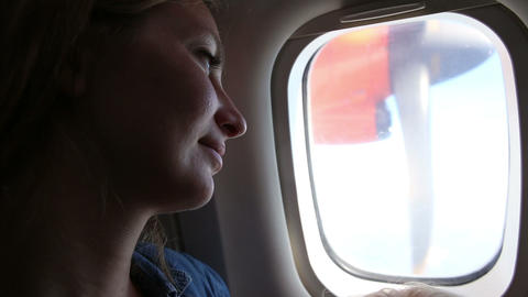 woman smile and looks out of plane window Footage