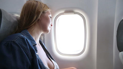 Young Girl Looks Out Of Plane Window stock footage