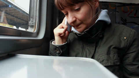 Woman talking on the phone in a train Footage