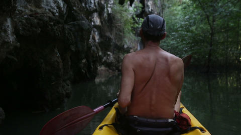 elder tanned man floating on kayak Live Action