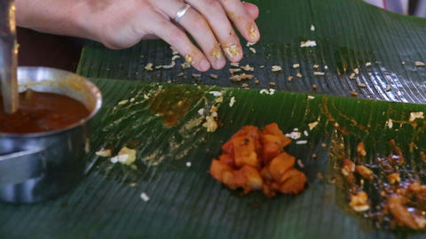 man eats up food and rolls up banana leaf Footage