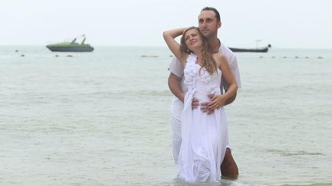 groom embraces blonde bride from back Footage