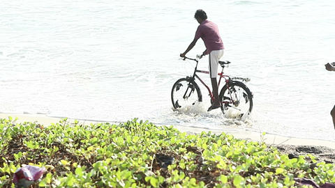 indian guys ride bike along waves of sea Footage