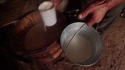 hand pours a glass of milk from a wooden barrel in Footage